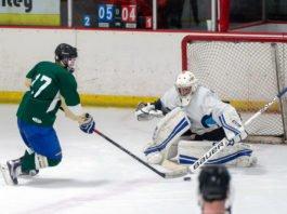 beer league hockey player shooting on goal